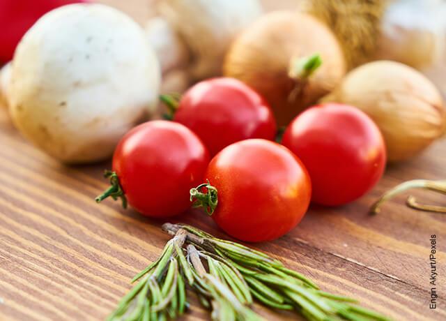 Foto de tomates, cebollas y especias sobre una mesa que muestran la salsa napolitana y su receta