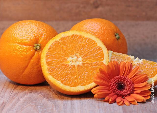 Foto de naranjas enteras y partidas sobre una mesa