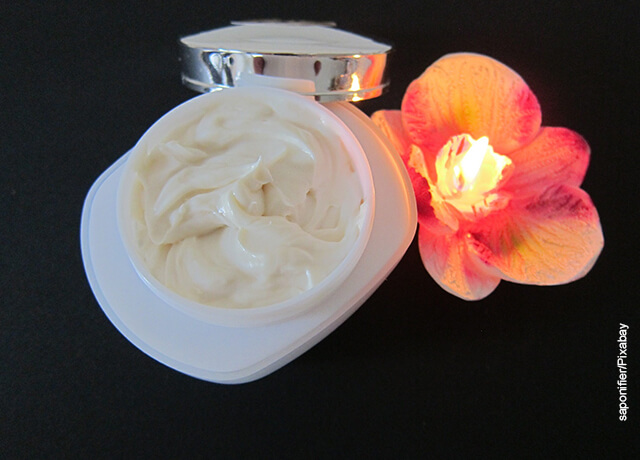 Foto de una crema para el rostro junto con una vela en forma de flor