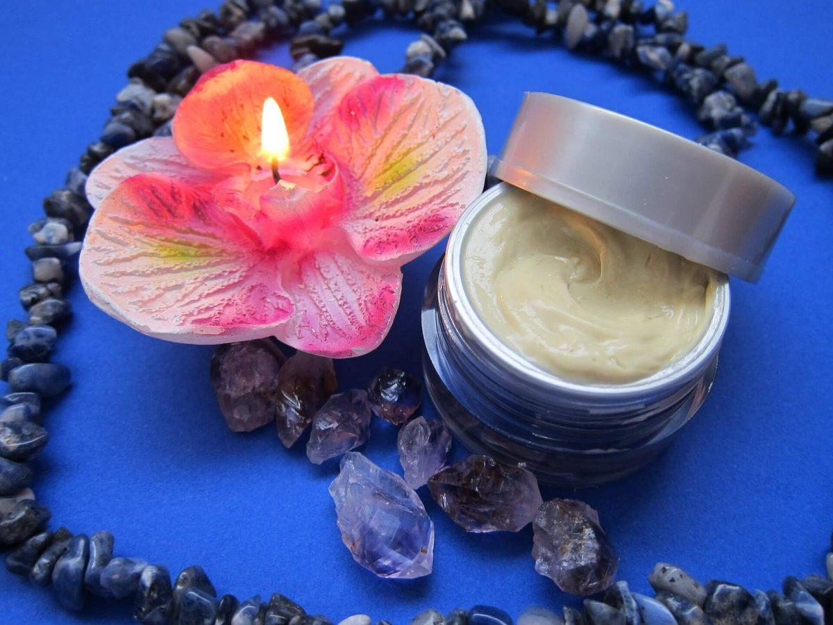 Foto de un recipiente con crema junto con una vela en forma de flor