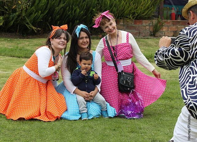 Foto de unas mujeres vestidas con trajes de colores posando para una foto