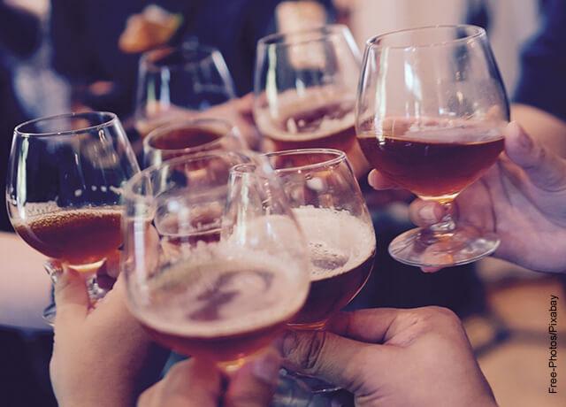 Foto de unas personas brindando con copas de cerveza