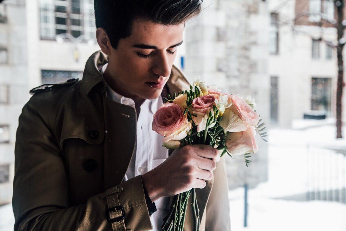 Foto de un hombre con un ramo de rosas rosadas que muestra lo que es soñar con flores