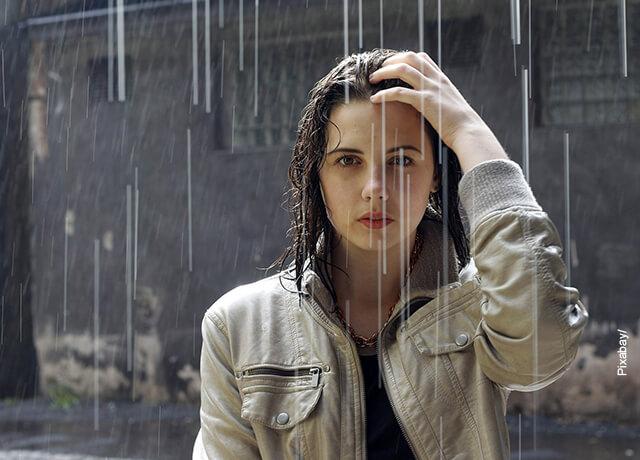 Foto de una mujer joven mojándose bajo un aguacero
