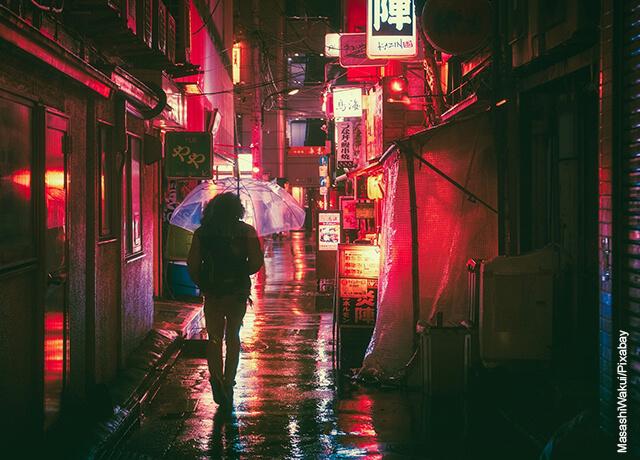 Foto de una persona caminando bajo la lluvia en la noche