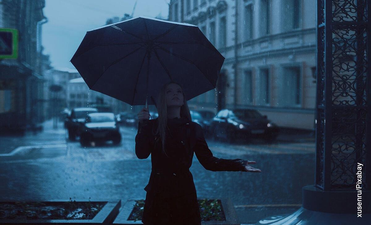 Foto de una mujer vestida de negro bajo un aguacero que ilustra lo que significa soñar con lluvia