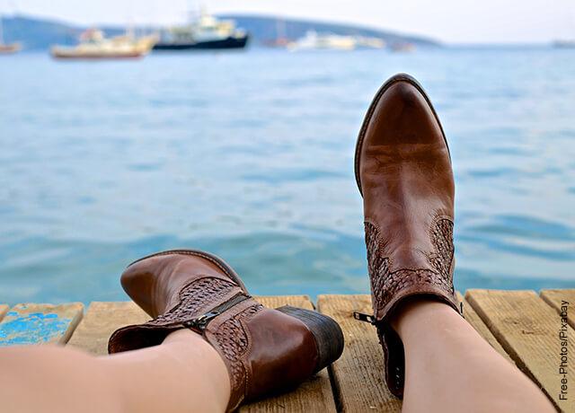 Foto de los pies de una mujer con unas botas cafés que muestran lo que es soñar con zapatos