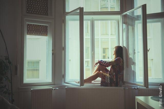 foto de una mujer triste y sola en la ventana