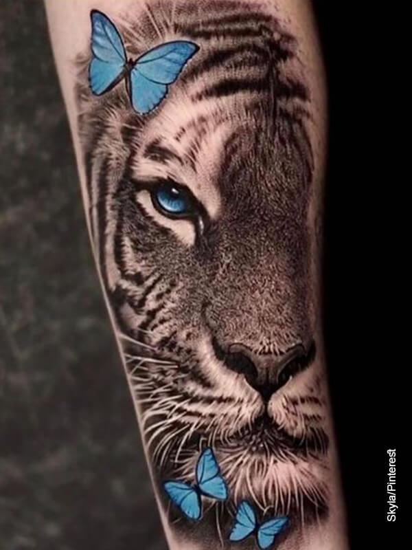 Foto del tatuaje de una leona con mariposas en un brazo