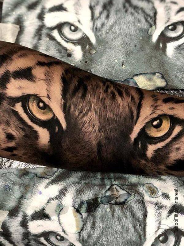 Foto de los ojos de un tigre tatuados en un brazo