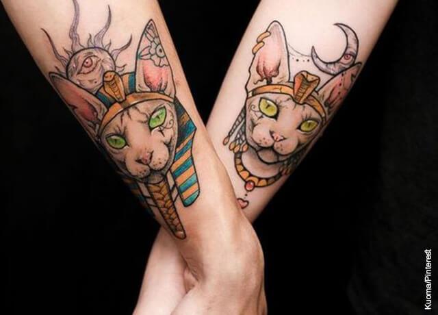 Foto de dos manos entrelazadas con tatuajes de gatos que muestra los tatuajes egipcios