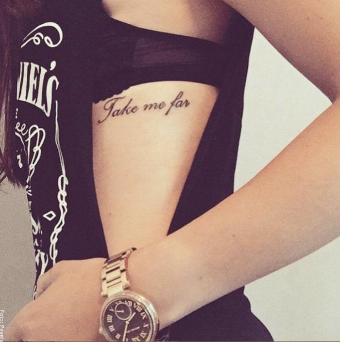 Foto de mujer con tatuaje de frase en el costado