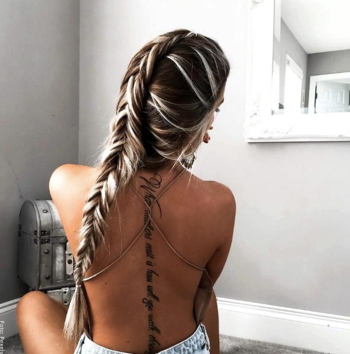 Foto de mujer con tatuaje en el centro de la espalda