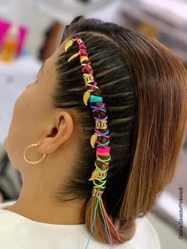 Foto de una joven con una trenza enredada con hilos de colores