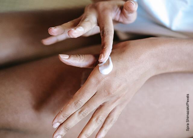 Foto de una mujer aplicando crema en sus manos