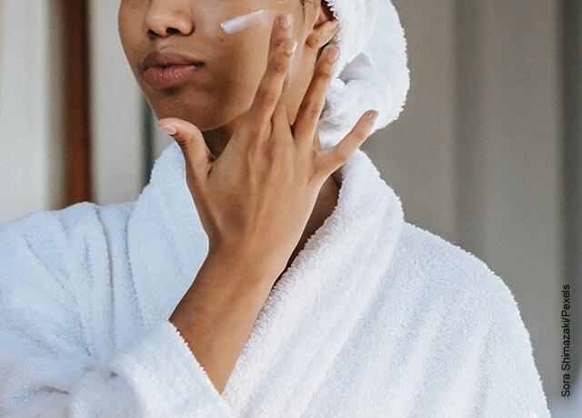 Foto de una mujer aplicando crema en una de sus mejillas