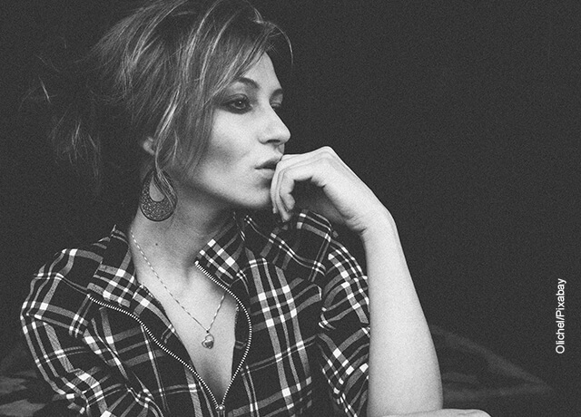Foto de una mujer en posición pensativa que ilustra cómo atraer a un hombre