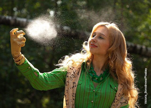 Foto de una mujer aplicándose perfume