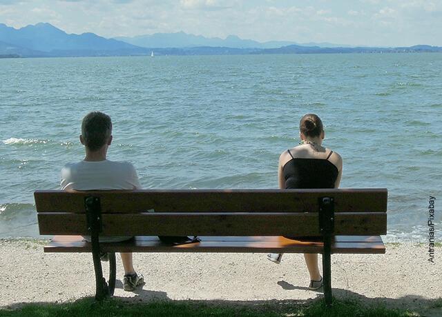Foto de dos personas sentadas en una banca frente al mar