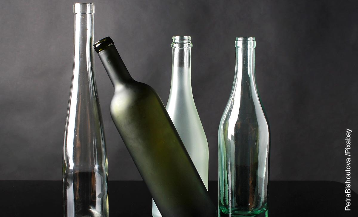 Foto de 4 envases sobre una mesa que muestra cómo decorar botellas de vidrio