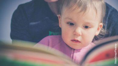 Foto de una niña con su padre que ilustra cómo enseñar a leer a un niño