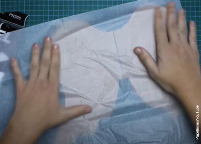 Foto de unas manos pegando un papel blanco sobre cartón