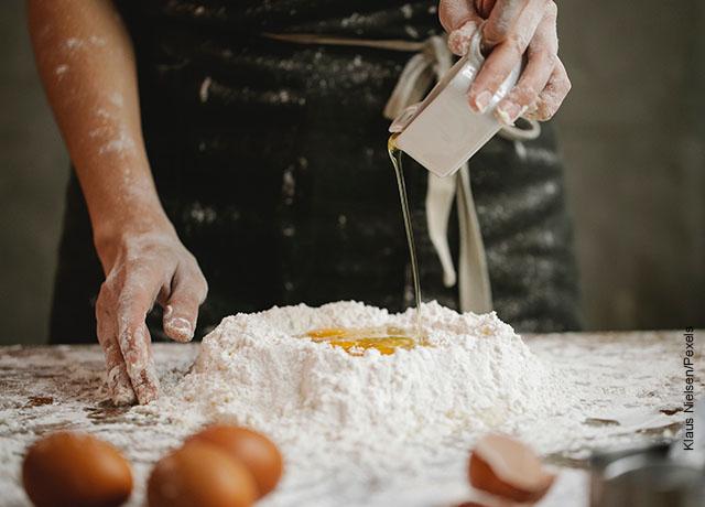Foto de un panadero vertiendo aceite a harina
