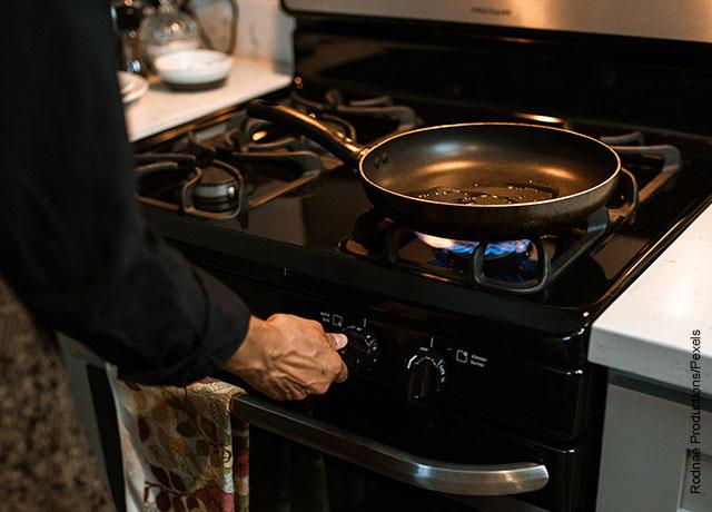 Foto de una persona calentando aceite en una sartén