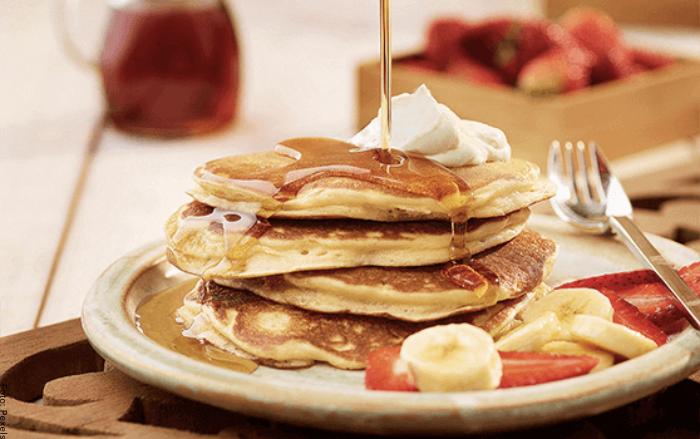 Foto de un plato con panqueques con miel, crema y frutas