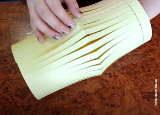 Foto de unas manos sobre un farol hecho en cartulina