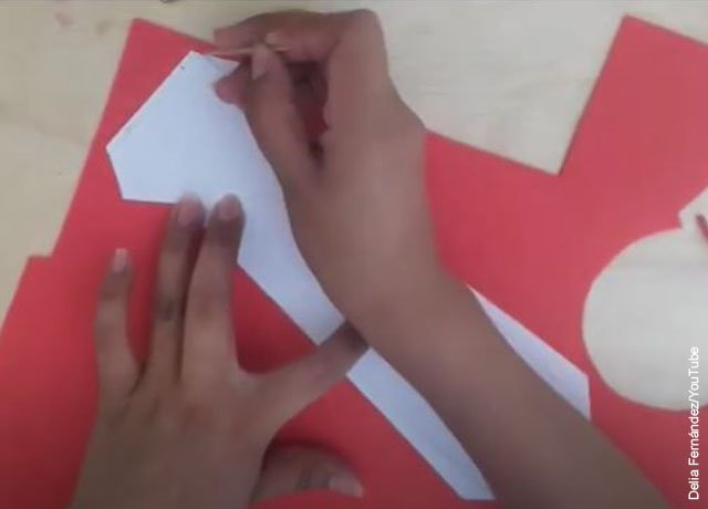 Foto de unas manos dibujando sobre un papel que ilustra cómo hacer una corbata