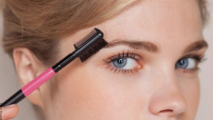 Foto de una mujer arreglándose las cejas