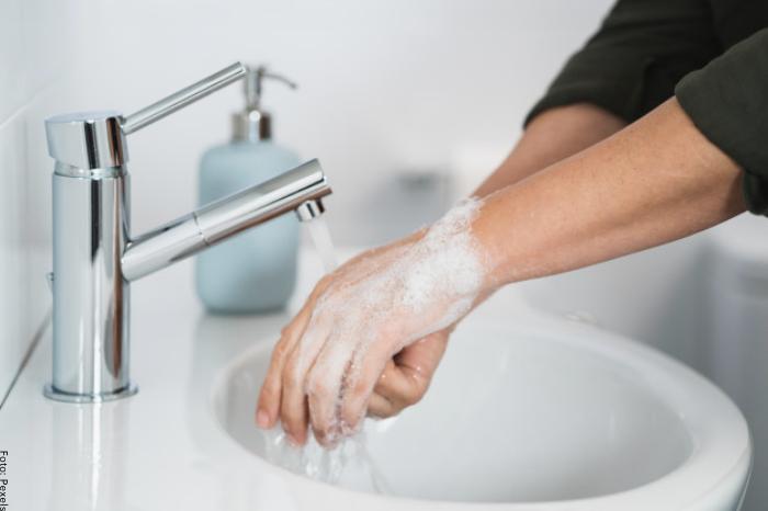 Foto de una mujer lavándose las manos con agua y jabón