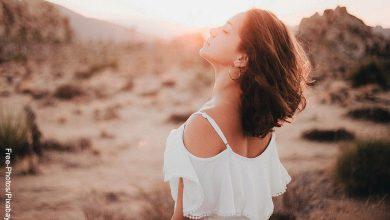 Foto de una mujer con los ojos cerrados respirando al aire libre que ilustra los cortes de cabello