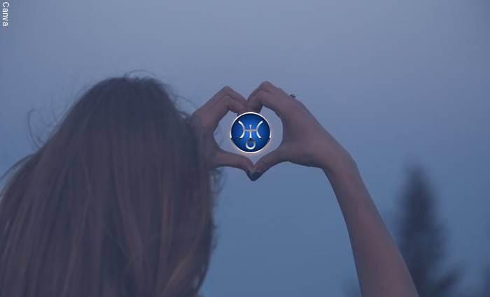 Una mujer de espaldas haciendo un corazón con las manos