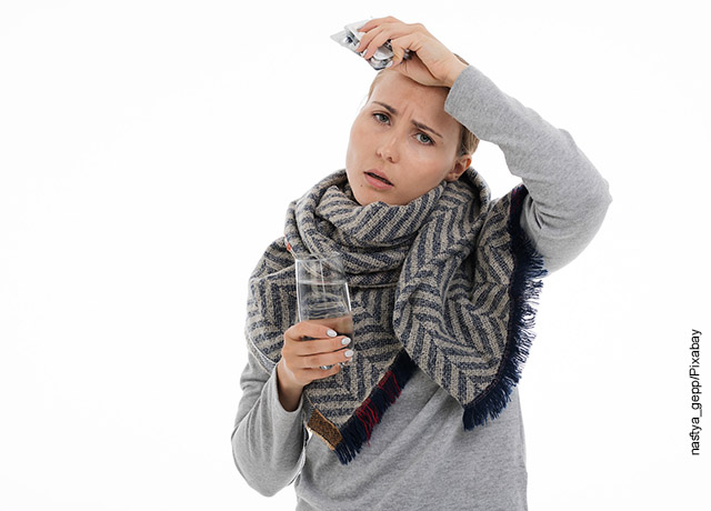 Foto de una mujer tomándose la cabeza con molestias