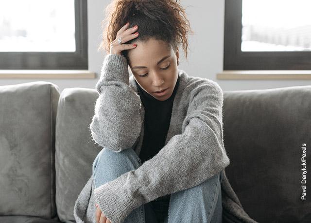 Foto de una mujer sentada en un sofá con una mano en su cabeza