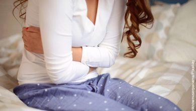 Foto de una mujer joven tomando su estomago que muestra el dolor de vientre bajo sin menstruación