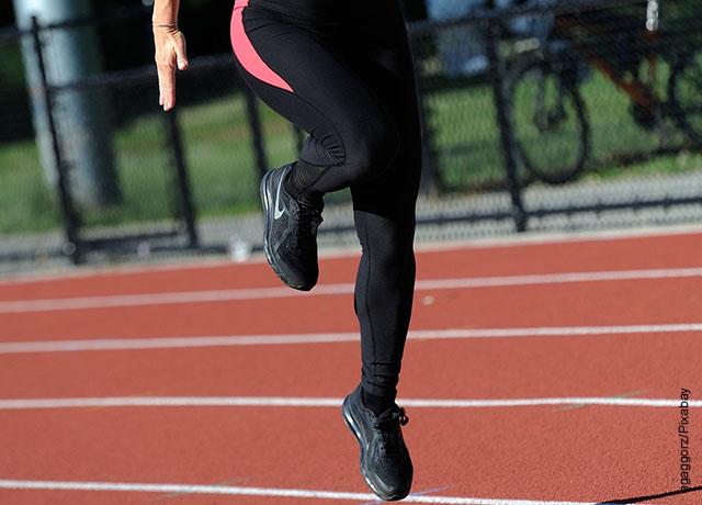 Foto de una mujer saltando en una pista de atletismo