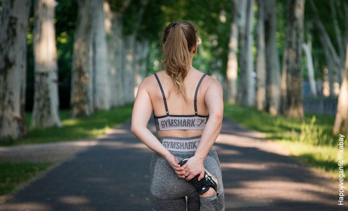 Foto de una jumer estirando antes de correr que muestra los ejercicios cardiovasculares en casa