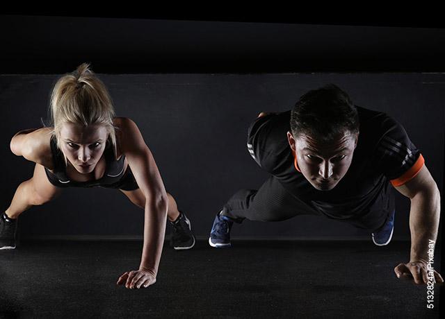Foto de un hombre y una mujer haciendo flexiones de pecho