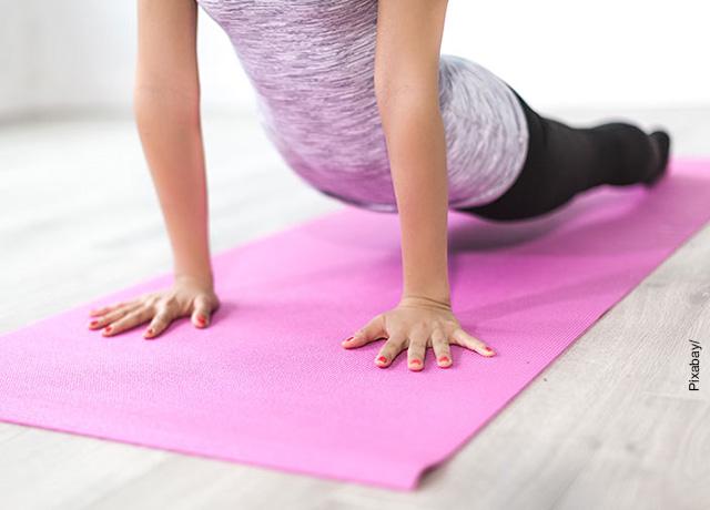 Foto de una mujer haciendo un ejercicio sobre una colchoneta