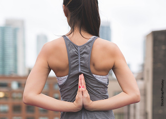 Foto de una mujer juntado sus manos en la espalda