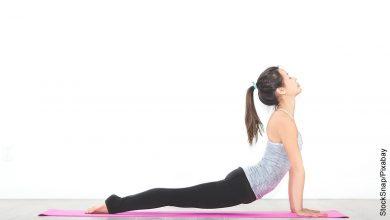 Foto de una mujer acostada en una colchoneta que muestra ejercicios lumbares en casa