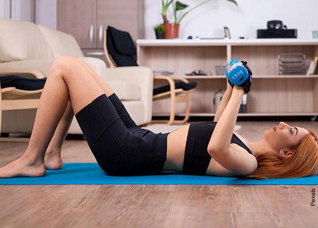 Foto de una mujer tumbada en el piso que muestra los ejercicios para pecho en casa