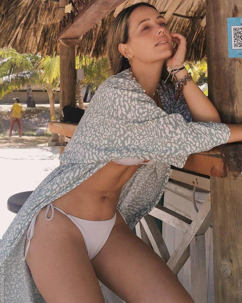 Foto de Milena López en bikini y detrás de ella en el paisaje aparece un hombre sin pantalones
