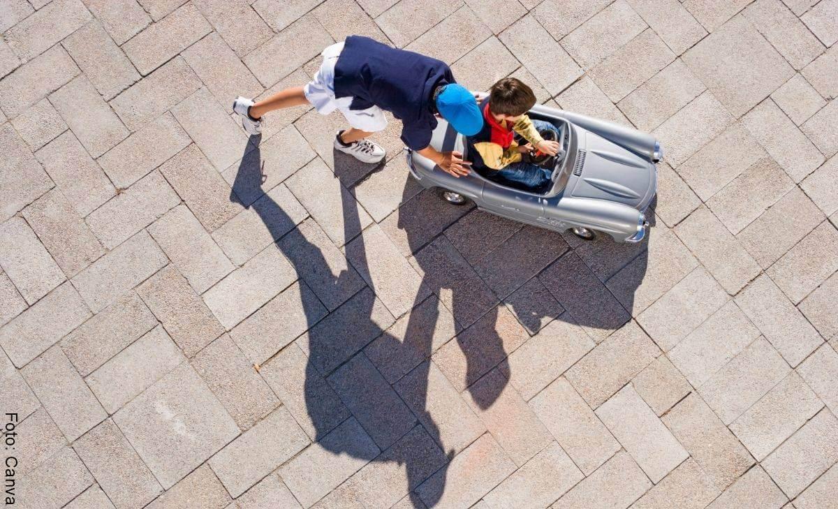 Hombre conduce carrito de juguete en calles repletas de carros