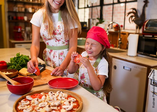 Foto de una niña cocinando con su mamá y probando algo ácido