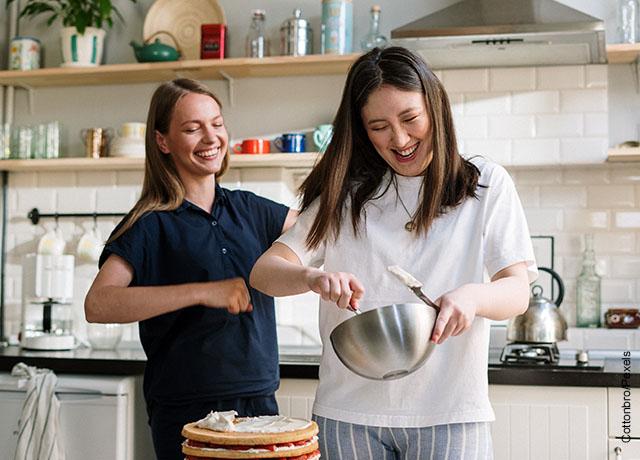 Foto de dos amigas cocinando juntas y riendo