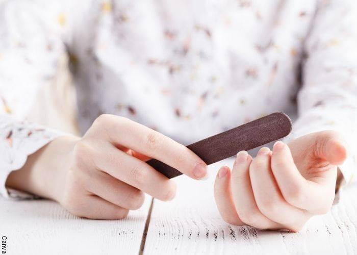Foto de una mujer limándose las uñas